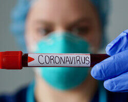 "Close-up of a vial of blood labeled with ""coronavirus,"" being held by a healthcare professional wearing protective gloves, mask, and headwear."