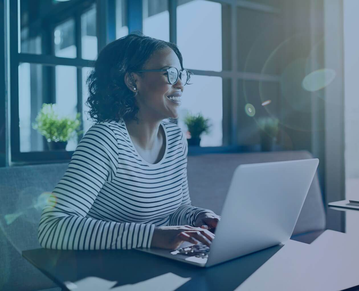 A black woman in glasses at her computer screen smiling.