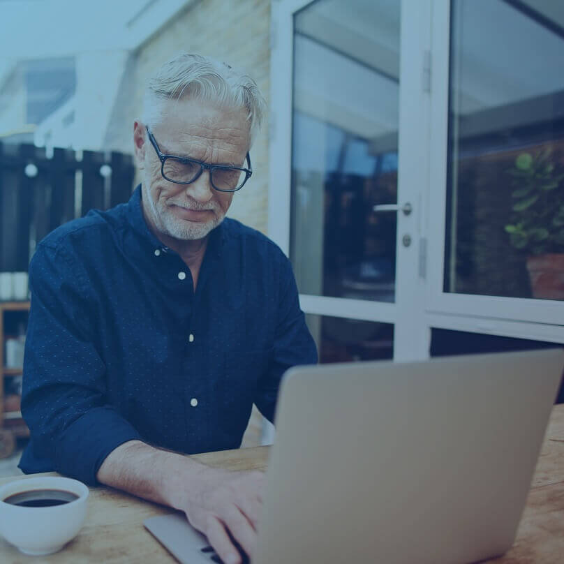 An older Caucasian man in glasses with a cup of coffee, using his laptop and smiling.