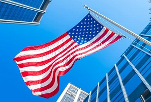 Upward view of an American flag flying with a bright blue sky and modern office buildings.