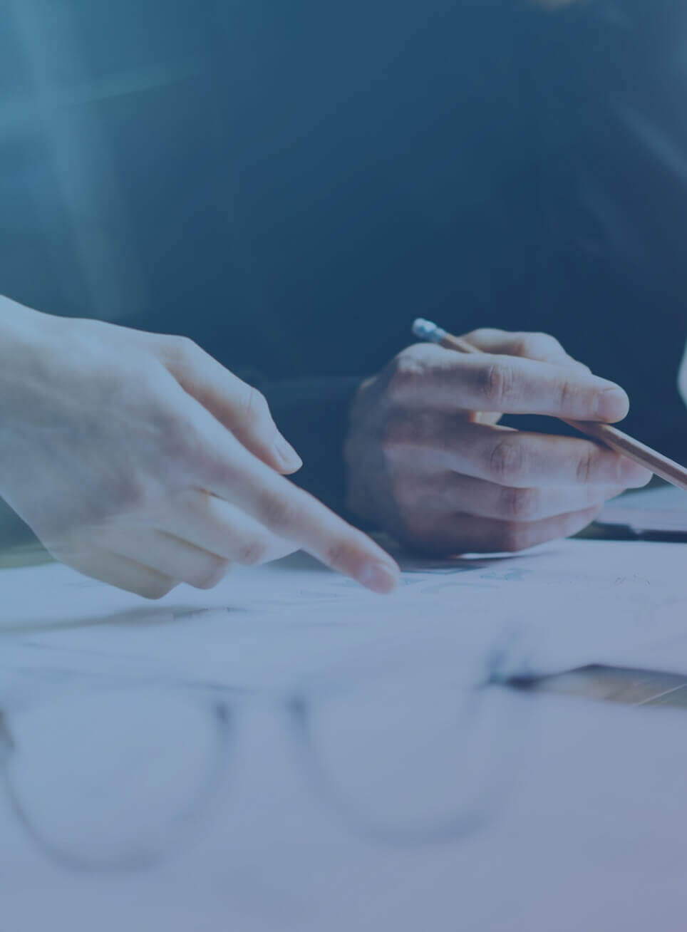 Two people's hands with documents, a pen, and eyeglasses on a table.