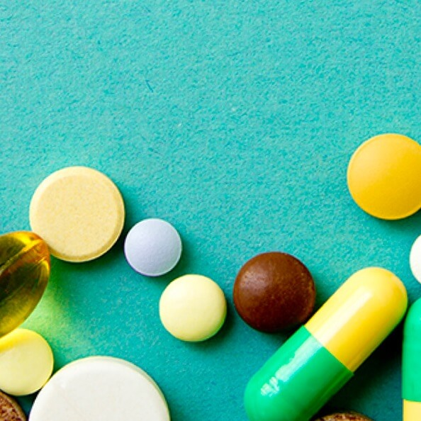 About a dozen different vitamins or supplement tablets and capsules on a teal background.