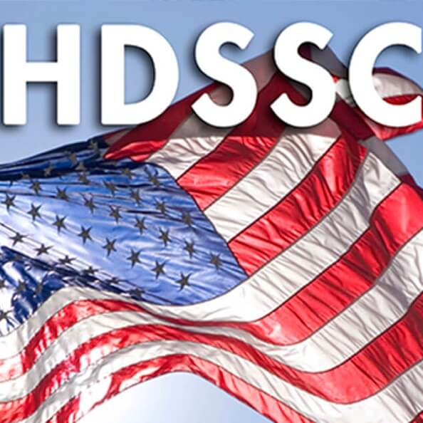 The logo for ANSI's HDSSC program, featuring a close-up American flag waving in the wind against a bright sky.