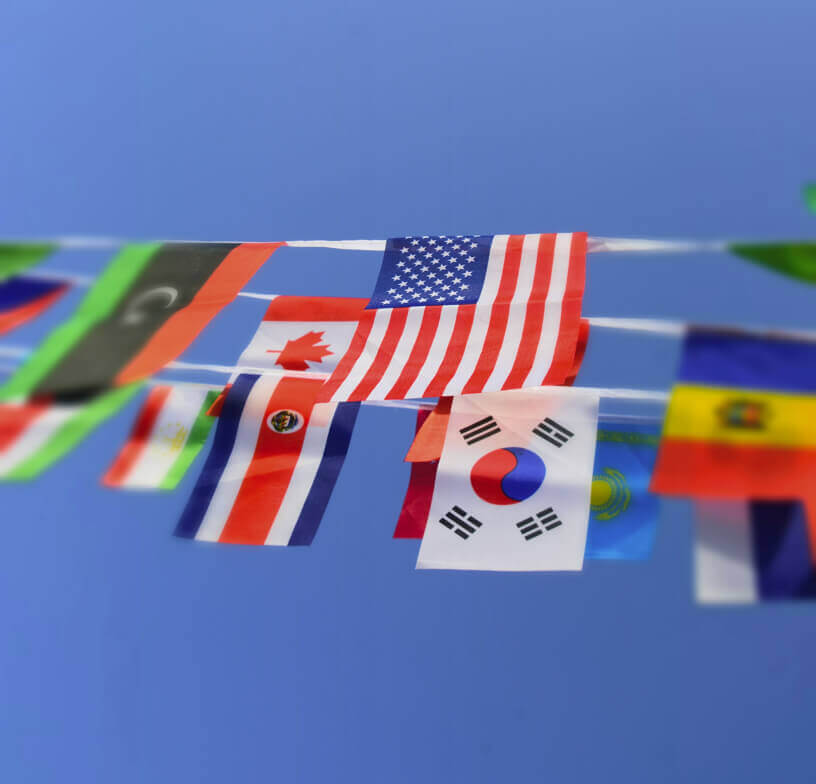 A group of international flags, including a U.S. flag, hanging from string banners.