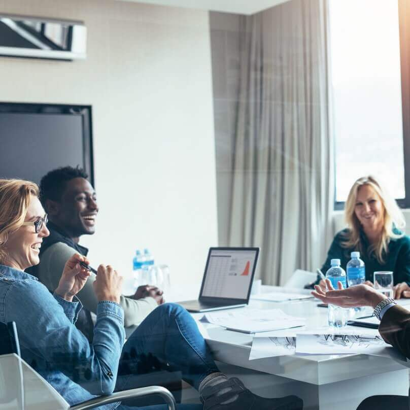 A small group of smiling people talking and working together in a meeting room with tablet computers and bottles of water.
