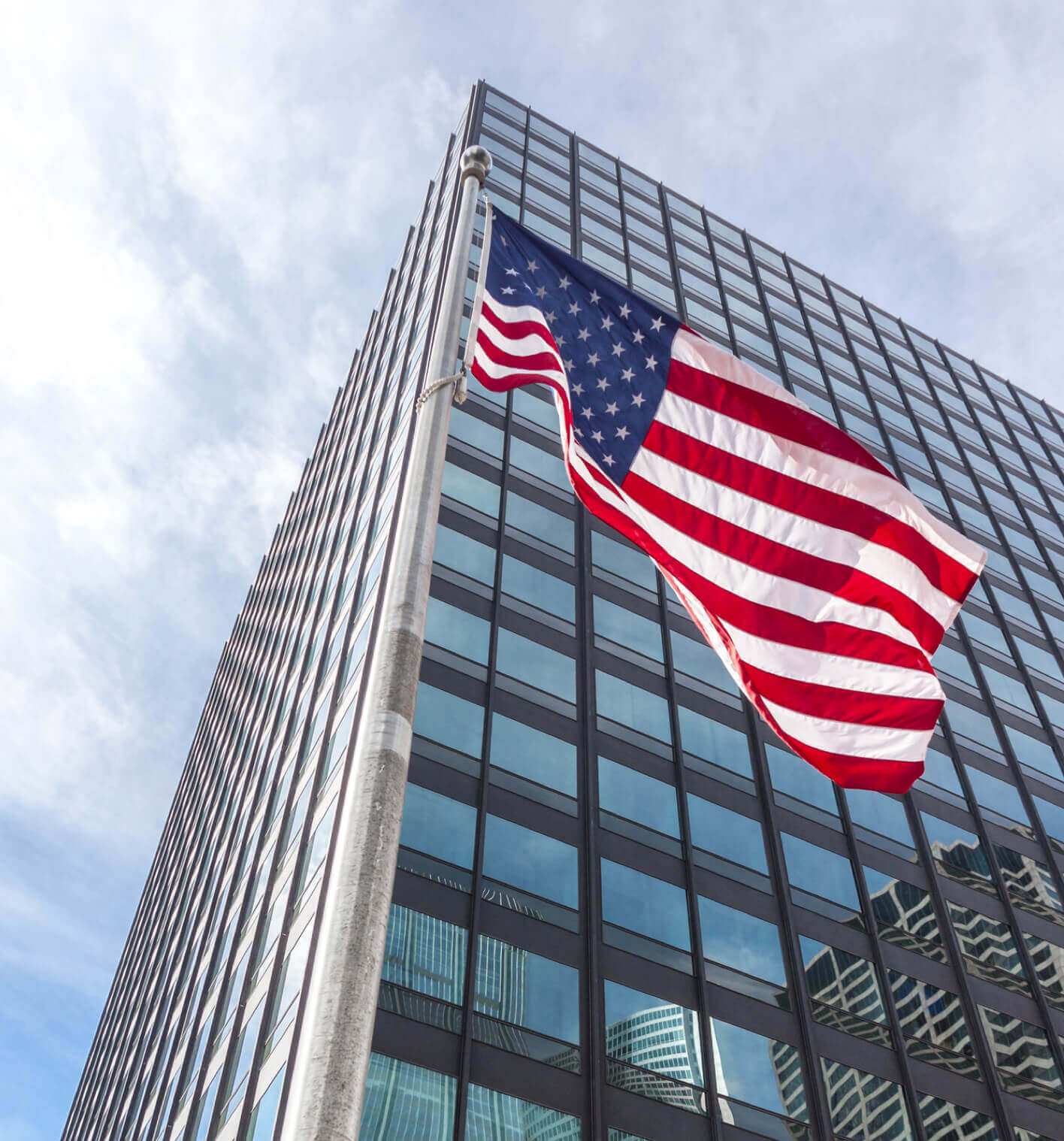 An upward view of an american flag flying in front of a modern office building and a bright sky.