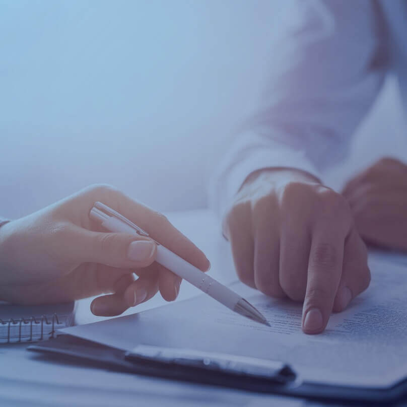 Two people's hands with a pen and a document being reviewed.