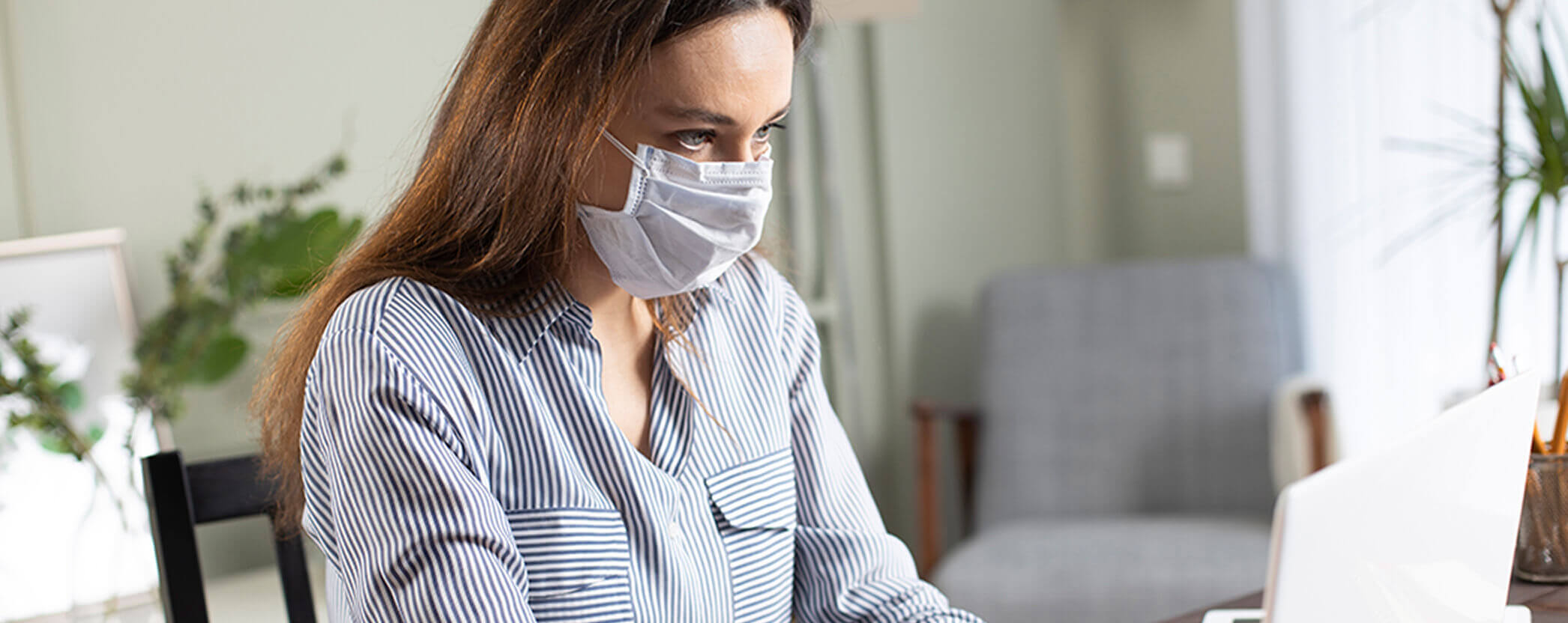 A female office worker wears a mask as she looks at her computer screen.