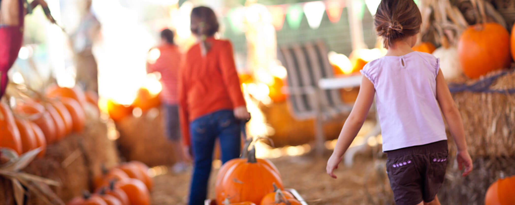 Kids carrying pumpkins at a fall festival.