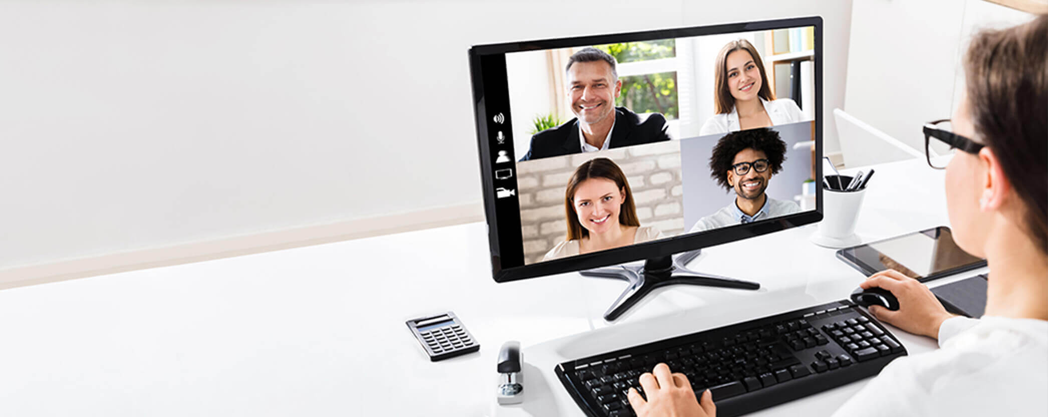 A woman at a desk particpating in a virtual meeting on her computer.